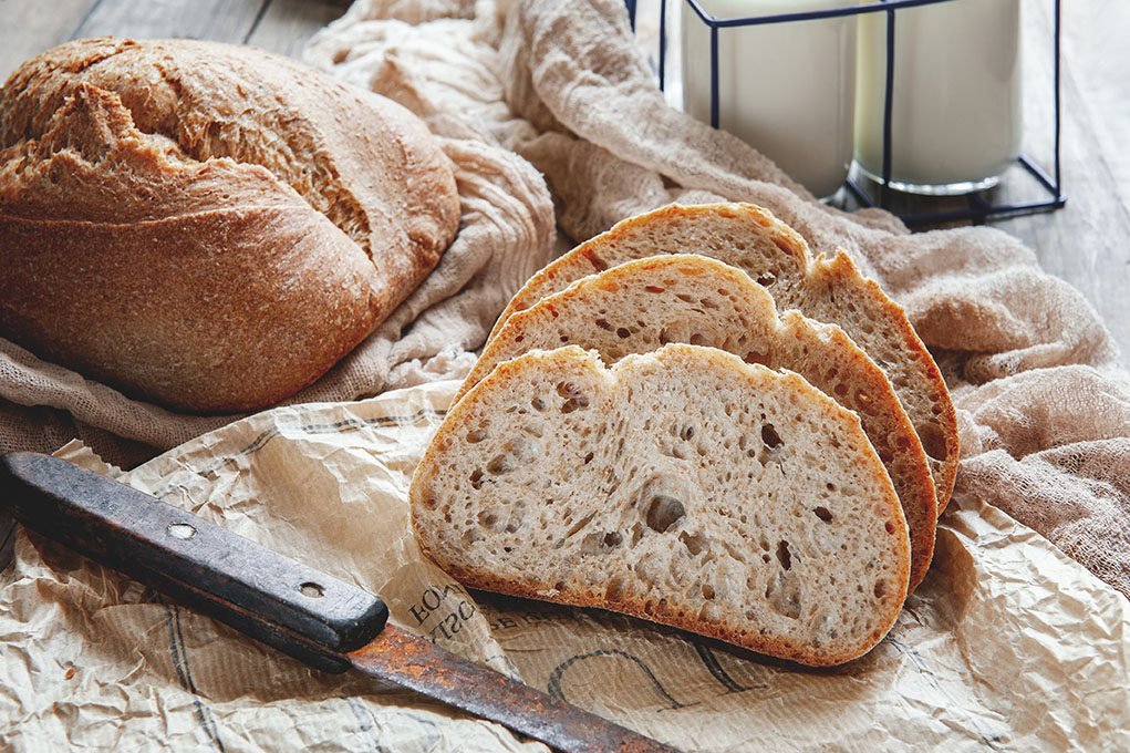 Delicious homemade sourdough rye bread on a plate and milk. Homemade baking